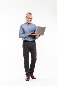 Vrolijke volwassen man in brillen met behulp van laptopcomputer
