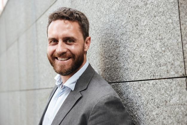Vrolijke volwassen man in grijs pak en wit overhemd met grote stralende glimlach, terwijl hij tegen een granieten muur staat