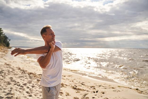 Vrolijke volwassen man warmt zich op voor de ochtendtraining door zijn armen uit te strekken op de kust