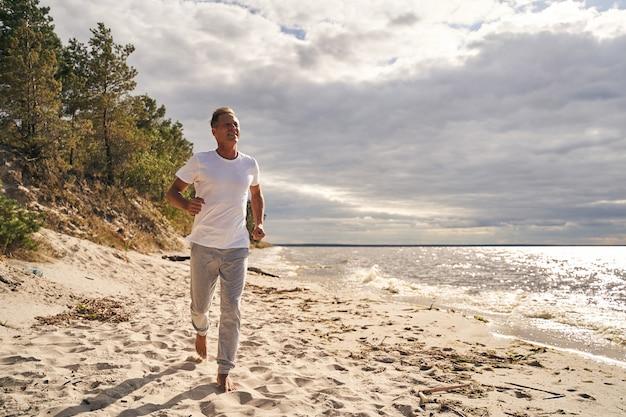 Vrolijke volwassen man warmt zich 's ochtends op door te joggen voor de training op het zonnige strand