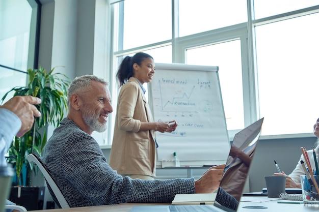Vrolijke volwassen man zit op een bijeenkomst in het moderne kantoor en glimlacht terwijl zijn jonge gemengde ras