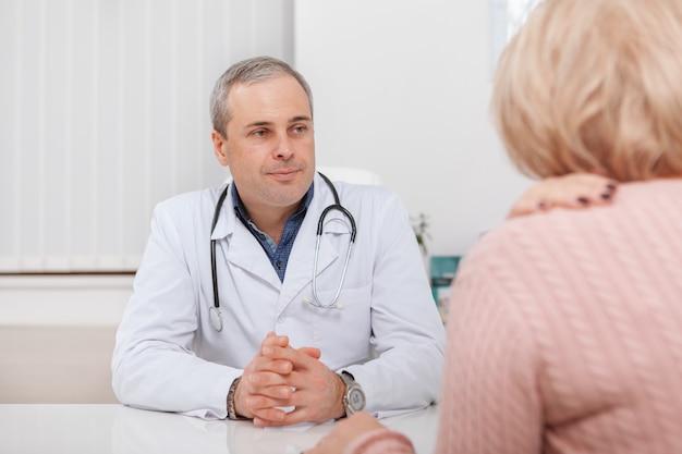 Vrolijke volwassen mannelijke arts die aan een patiënt spreekt