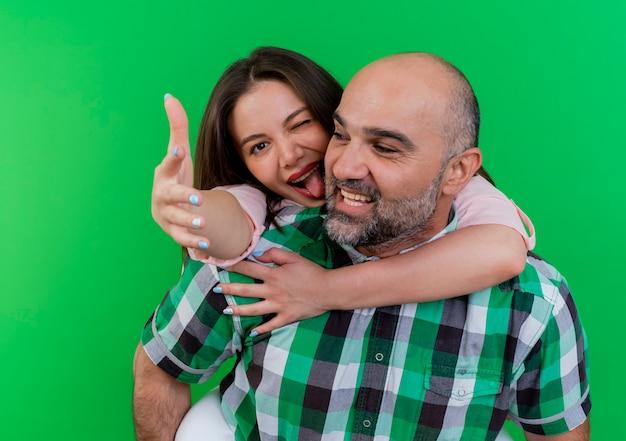 Vrolijke volwassen paar man kijken kant bedrijf vrouw op zijn rug vrouw knipogen weergegeven: tong uitrekken hand