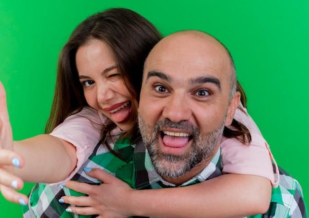Vrolijke volwassen paar man met vrouw op zijn rug vrouw knipogen weergegeven: tong uitrekken hand