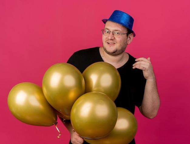 Vrolijke volwassen slavische man in optische bril met blauwe feestmuts houdt heliumballonnen vast