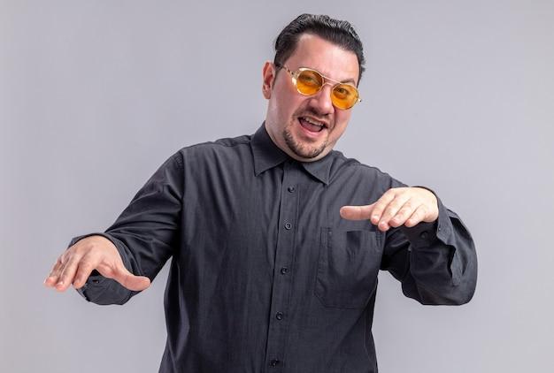Vrolijke volwassen slavische man in zonnebril die handen open houdt