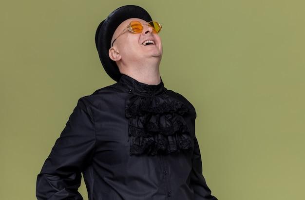 Vrolijke volwassen slavische man met hoge hoed en met zonnebril in zwarte gotische shirt opzoeken