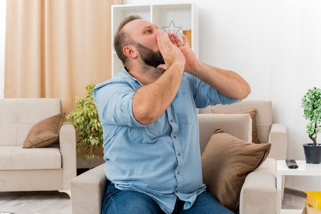 Vrolijke volwassen slavische man zit op een fauteuil en houdt zijn handen dicht bij de mond en kijkt naar de zijkant en doet alsof hij iemand belt in de woonkamer