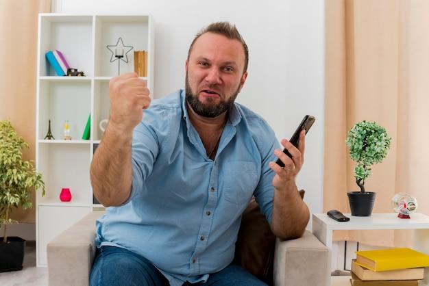 Vrolijke volwassen slavische man zit op fauteuil vuist houden en telefoon kijken camera in de woonkamer