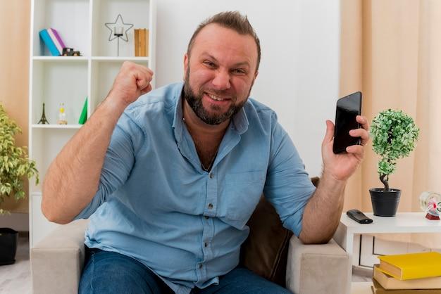 Vrolijke volwassen slavische man zit op fauteuil vuist omhoog te houden en telefoon vast te houden in de woonkamer