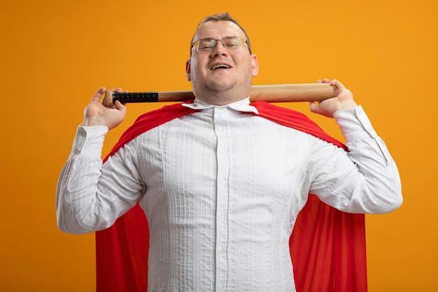 Vrolijke volwassen slavische superheld man in rode cape bril houden honkbalknuppel achter nek geïsoleerd op oranje muur