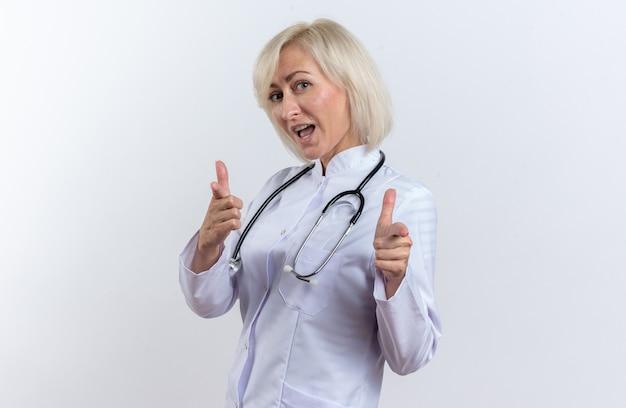Vrolijke volwassen slavische vrouwelijke arts in medische mantel met stethoscoop wijzend op camera geïsoleerd op een witte achtergrond met kopie ruimte