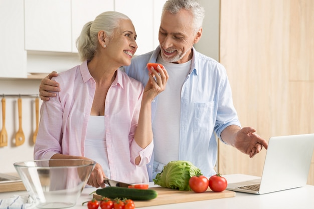 Vrolijke volwassen verliefde paar familie met behulp van laptop en koken