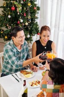 Vrolijke volwassen vrienden roosteren met glazen wijn en sap bij het vieren van nieuwjaar thuis