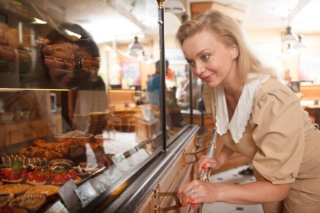Vrolijke volwassen vrouw die naar desserts kijkt in de detailhandel in de bakkerijwinkel