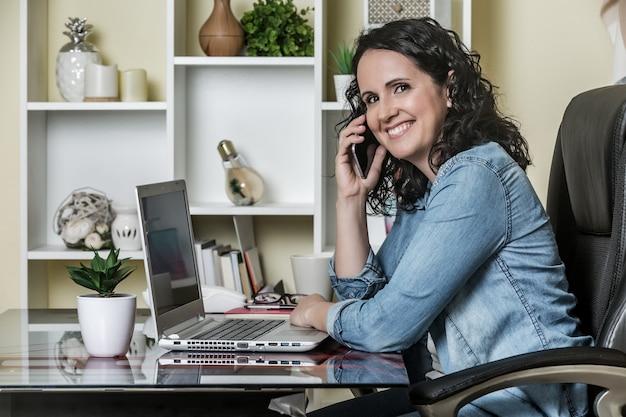Vrolijke volwassen vrouw die telefoneert terwijl het werken aan laptop in modern bureau