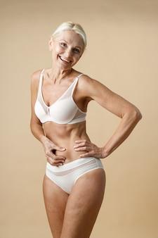 Vrolijke volwassen vrouw in ondergoed met een fit lichaam dat lacht naar de camera en haar huid aanraakt en hand vasthoudt