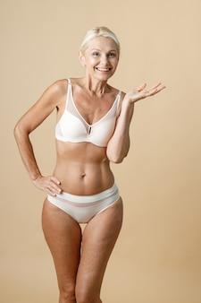 Vrolijke volwassen vrouw in ondergoed met een fit lichaam dat naar de camera glimlacht en hand op haar middel houdt