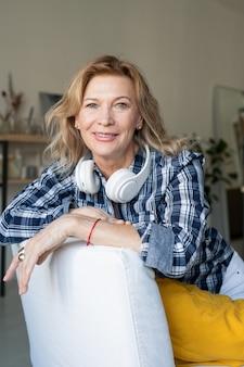 Vrolijke volwassen vrouw met koptelefoon op nek zitten in witte lederen fauteuil