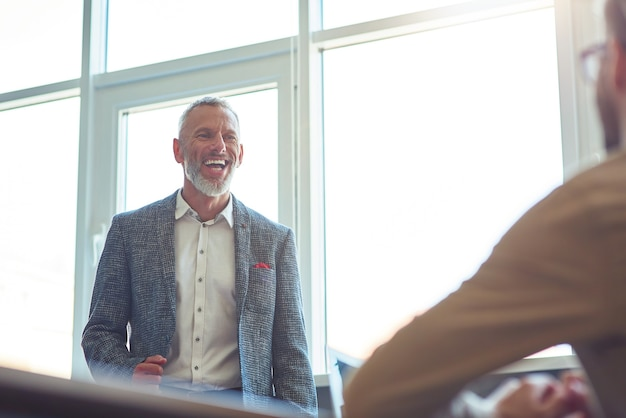 Vrolijke volwassen zakenman die iets bespreekt met zijn jonge mannelijke collega en glimlacht terwijl