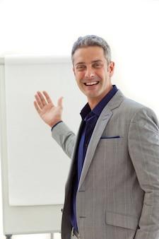 Vrolijke volwassen zakenman wijzend op een bord