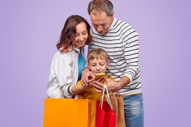 Vrolijke volwassene en zoon met papieren zakken die samen op smartphone browsen terwijl ze tegen een paarse achtergrond staan en winkelen