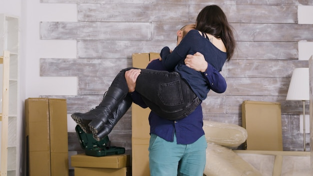 Vrolijke vriend die zijn vriendin ronddraait in hun nieuwe appartement. paar verhuizen in nieuw appartement.