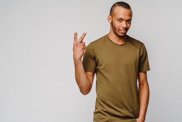 Vrolijke vriendelijke afro-amerikaanse jonge man in groen t-shirt met twee met vingers