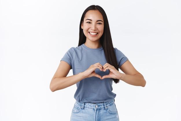 Vrolijke, vriendelijke en enthousiaste charmante aziatische vriendin die zegt dat ik van je hou, een hartteken laat zien en glimlacht, bewondering bekent, een relatie koestert, een gelukkige valentijnsdag, een verrassing maakt