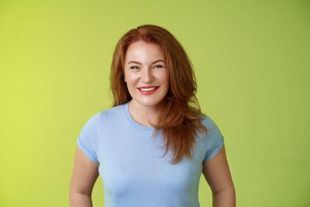 Vrolijke vriendelijke gelukkige roodharige moeder van middelbare leeftijd kijken zorgzaam opgetogen glimlachend breed staren bewondering vreugde staan blauw t-shirt groene muur geamuseerd enthousiaste uitdrukking