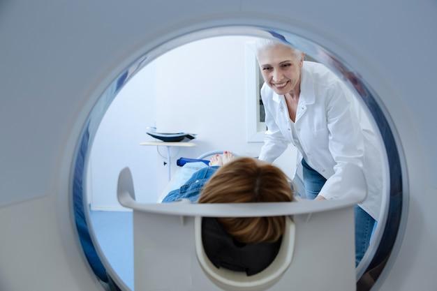 Vrolijke vriendelijke professionele arts die haar patiënt bekijkt en lacht tijdens de voorbereiding van haar op medisch onderzoek