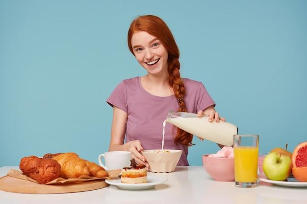 Vrolijke vriendelijke vrolijke roodharige vrouw aan de tafel gaat ontbijten