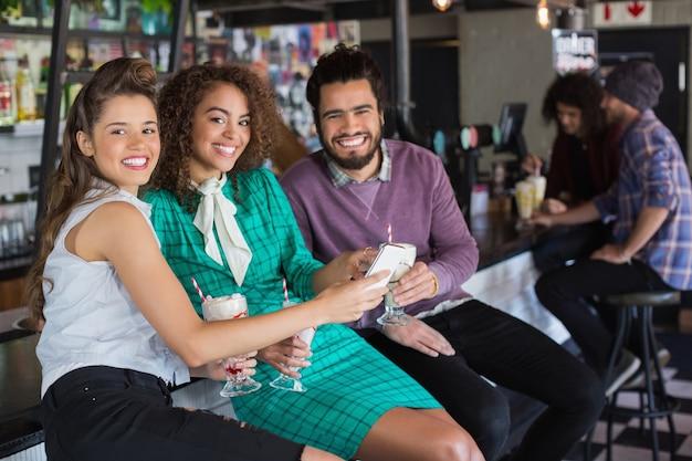 Vrolijke vrienden bespreken via mobiel terwijl het hebben van een drankje in restaurant