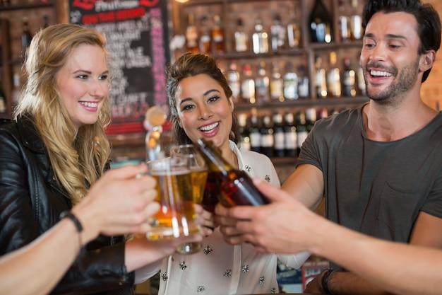 Vrolijke vrienden die bierpullen en flessen roosteren