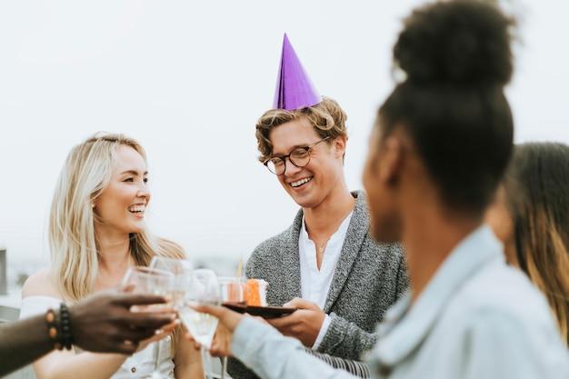 Vrolijke vrienden die bij een partij van de dakverjaardag vieren