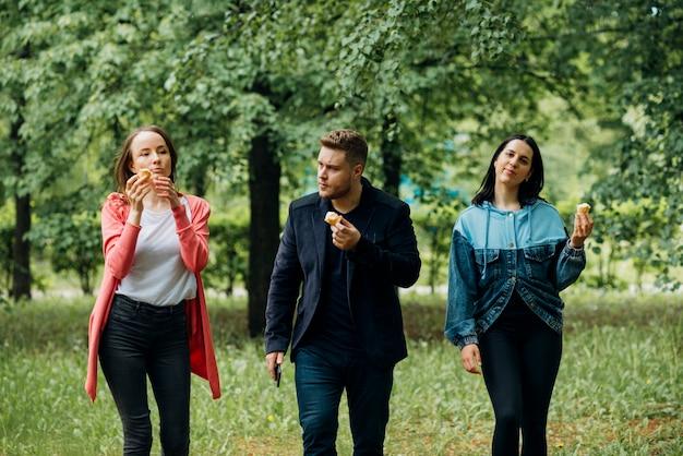 Vrolijke vrienden die in park met roomijs lopen