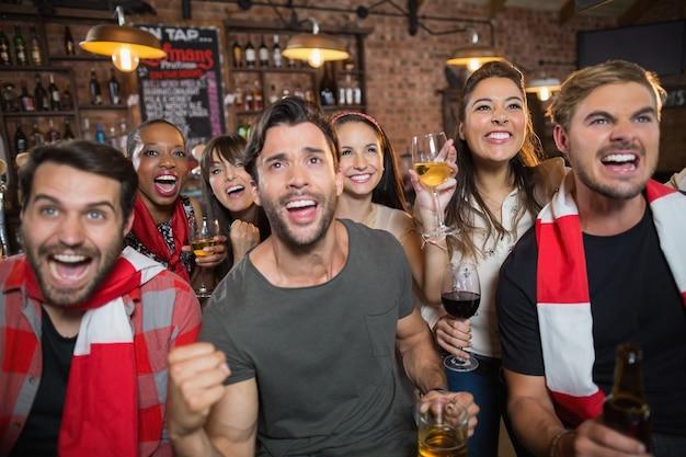 Vrolijke vrienden die in pub genieten
