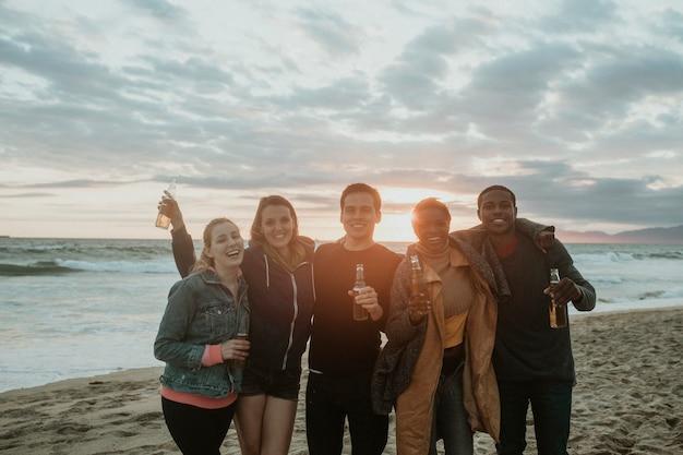 Vrolijke vrienden die op het strand drinken