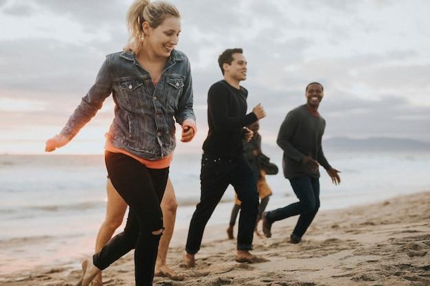 Vrolijke vrienden die op het strand rennen