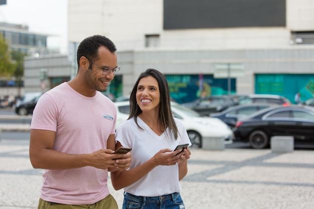 Vrolijke vrienden die op straat met smartphones wandelen