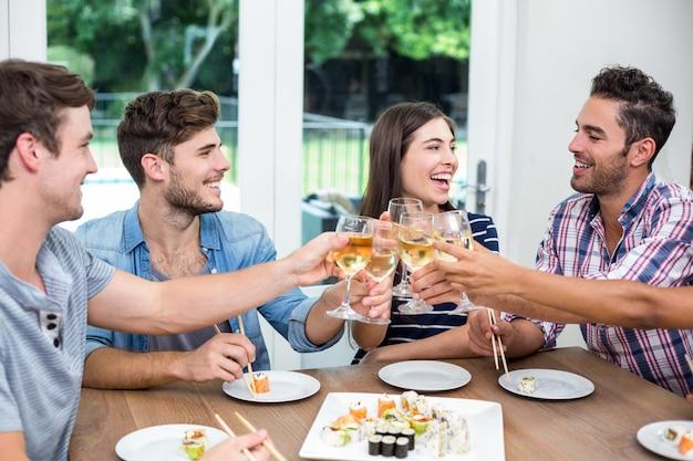 Vrolijke vrienden die wijn roosteren terwijl het hebben van sushi