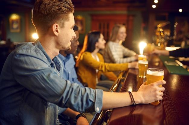 Vrolijke vrienden drinken bier aan het loket in de bar
