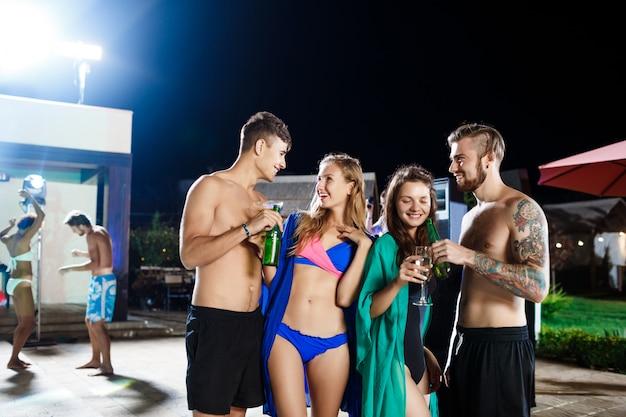 Vrolijke vrienden glimlachen, vreugde, rust op feestje in de buurt van zwembad