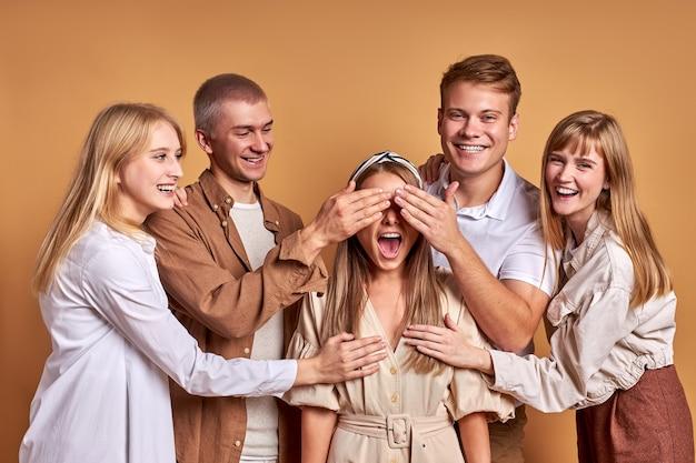 Vrolijke vrienden hebben plezier, lachen samen geïsoleerd op bruine studio achtergrond. gelukkige tijd doorbrengen