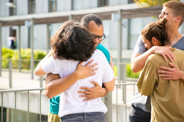 Vrolijke vrienden knuffelen buitenshuis
