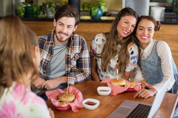 Vrolijke vrienden met hamburger in restaurant