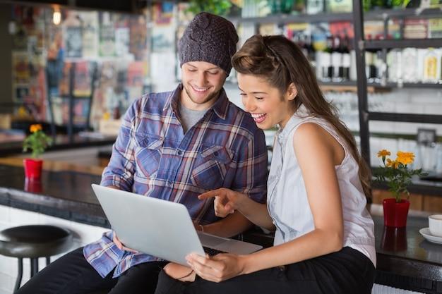 Vrolijke vrienden met laptop in restaurant