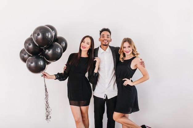 Vrolijke vrienden met zwarte ballonnen tijdens thuisfeest