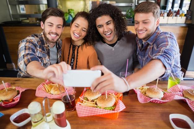 Vrolijke vrienden nemen selfie in restaurant