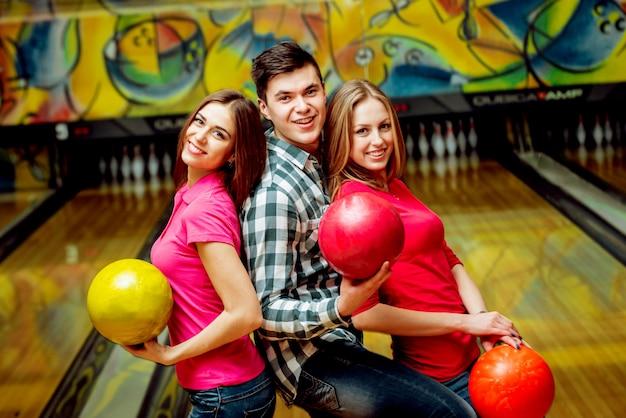 Vrolijke vrienden op de bowlingbaan met de ballen.